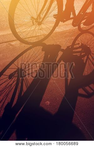 Shadow of unrecognizable cyclist riding a bike on road through city street in urban surrounding retro toned