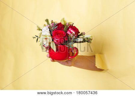 Hand holds a small red vase with flowers breaking through a yellow background, space for text