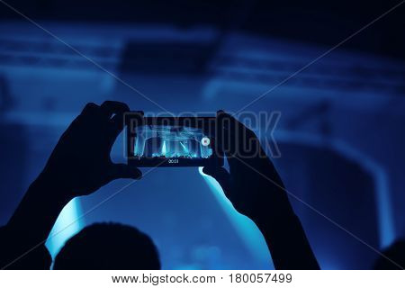 Hands with smartphone recording footage on live rock concert selective focus