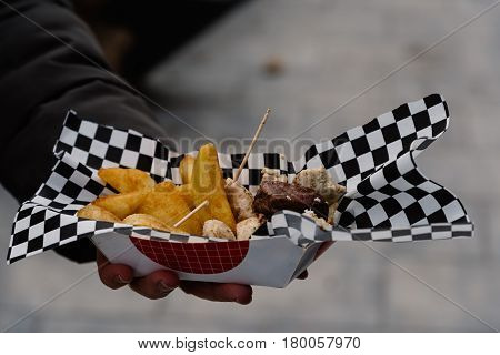 Midsection Of man Holding Street Food with meat and french fries. Focus on foreground