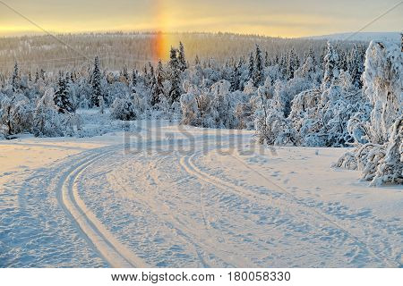 Snowy road and mountains heavily covered with fresh snow against the blue sky and clouds. Sun beam. Subpolar Urals, Russia