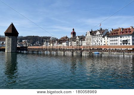 March 30 2017-Lucerne-Switzerland-panoramic view of the city of Lucerne and its lake popular with tourists who flock to its shores. In the foreground the famous covered bridge built in wood