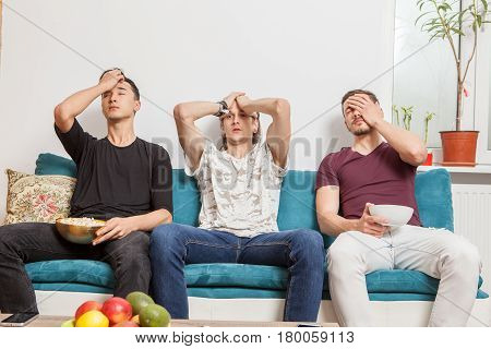 Group of friends watching together a ball game. Disappointed of their team lost