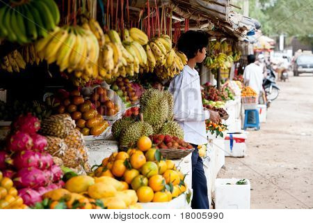 Young Man In Colorful Fruit Stand In Cambodian Market