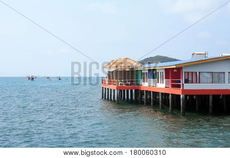 Bungalows on stilts against summer sea landscape with boats