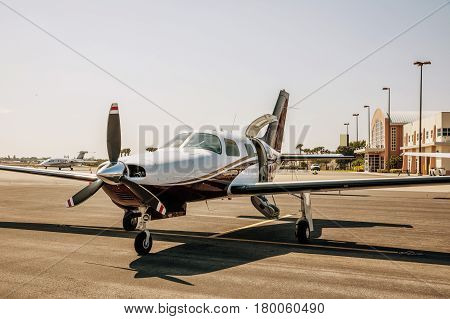 Private small single piston aircraft on airport runway. Small sports plane scrolls on the runway on a sunny day in Fort Myers Florida