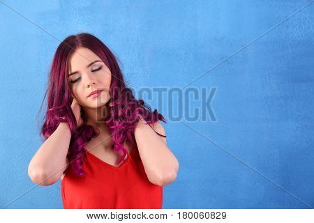 Beautiful young woman with dyed hair on color background