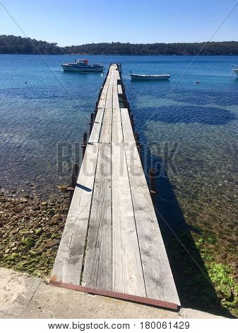 Wooden jetty leading into sea on Rab island
