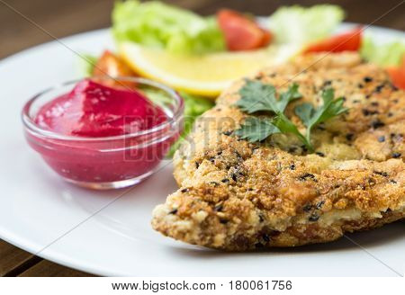 closeup of Homemade Breaded Schnitzel with salad and berry sauce on old wooden table