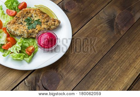 Homemade Breaded Schnitzel with salad and berry sauce on old wooden table. space for text