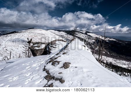 sandstone rock formation on Malinowska Skala hill with snow hills on the background and blue sky with clouds in winter Beskid Slaski mountains in Poland near Wisla resort