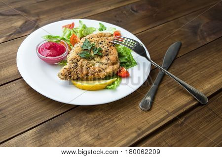 served Homemade Breaded Schnitzel with salad and berry sauce on old wooden table