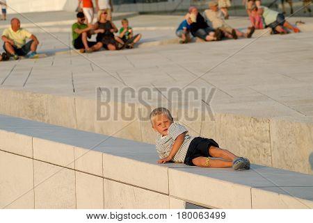 Oslo Norway - July 22 2014: Boy having rest near Oslo Opera House in sunny summer day