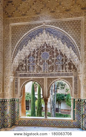 Window with stone relief with arabesques in Alhambra palace Spain