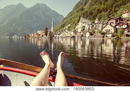 Beautiful view of young man relaxing on a traditional wooden rowing boat with Hallstatt lakeside town in the background on an idyllic sunny day in summer Salzkammergut Austria