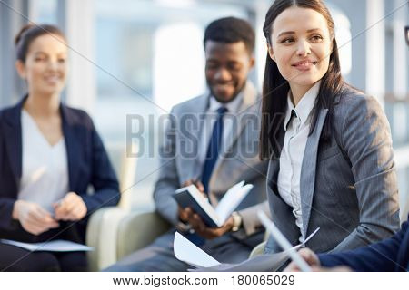 Young woman listening to her colleague during business training