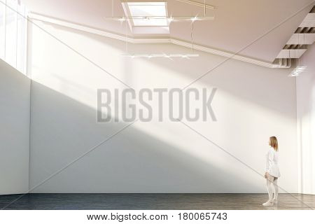 Woman walking near blank white wall mockup in modern gallery with sunrise. Girl admires a clear big stand mock up in museum with contemporary art exhibitions. Large hall interior, sunset from windows