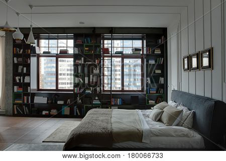 Modern bedroom with textured white and concrete walls. There is a bed with a coverlet and pillows, large bookcase with many books and a ladder, frames on the wall, hanging white lamps. Horizontal.