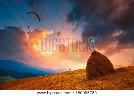 Paraglide Above The Valley With Haystack