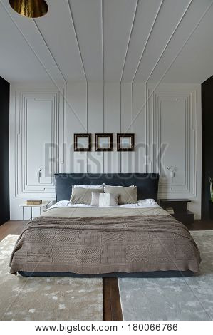 Contemporary bedroom with textured white walls and a parquet with carpets on the floor. There is a wide bed with a coverlet and pillows, small table with a book, black nightstand, frames over the bed.