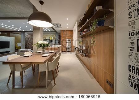 Kitchen zone in the studio apartment in a loft style with concrete columns. There is a long wooden table with chairs, kitchen island, white lockers, shelves with bottles, books and plants in the pots.