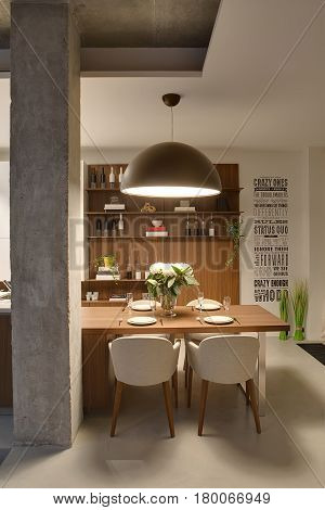 Luminous interior in a loft style with white walls with inscriptions and a concrete column. There is a wooden table with flowers and dishes, light chairs, shelves with bottles and books and plants.