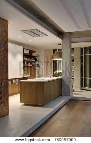 Glowing kitchen in a loft style with white walls and concrete columns. There is a kitchen island with a stove and a sink, white lockers, shelves with bottles and books and plants, big hanging lamp.