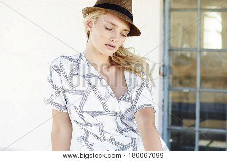 Young Beautiful blond in trilby looking down