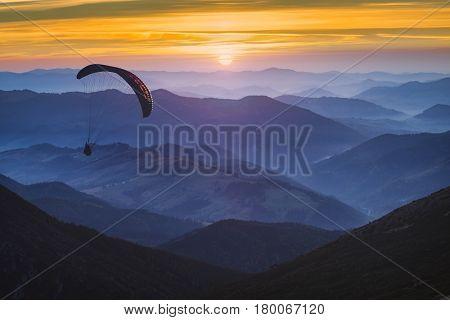Paraglide silhouette in a light of sunrise above the misty carpathian mountain valley.