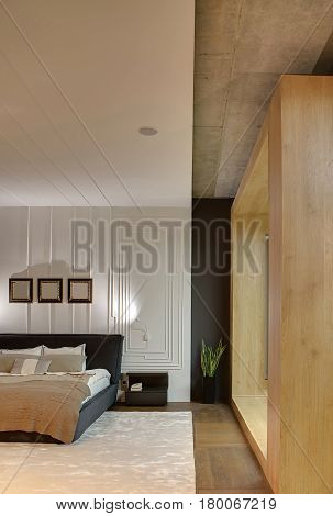 Bedroom in a loft style with textured white wall and a parquet with a carpet on the floor. There is a bed with pillows and a coverlet, dark nightstand, plant in a pot, luminous lamps, wooden entrance.