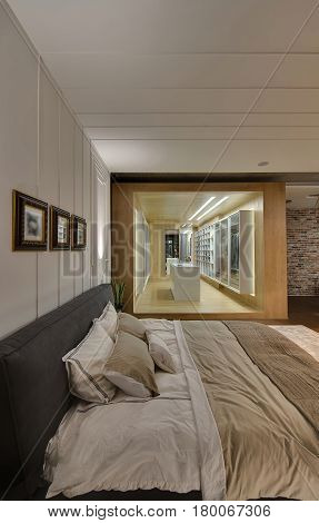 Large bed with pillows and coverlet on the background of the walk-in closet with wooden walls and white wardrobes. There are white textured walls with hanging frames, parquet with carpet on the floor.