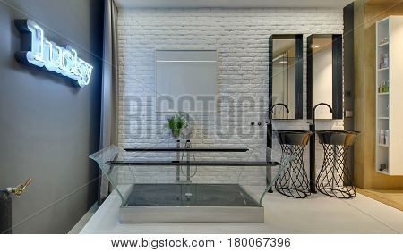 Luminous modern bathroom with gray and white brick walls. There is a glass bath, two dark reticulated sinks with mirrors, glowing signboard, white shelves with accessories on the wooden wall.