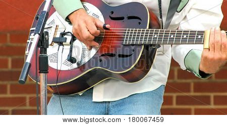 Male jazz guitarist performing in concert outdoors.