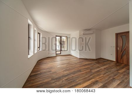 Empty room with natural light from windows.Modern house interior. Wooden floor.