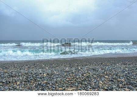 Waves, stormy sky and pebble beach.  Taken in Limassol, Cyprus on a stormy day.