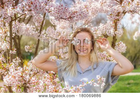Young woman covering her eyes with fresh colorful flowers.