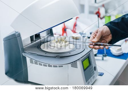 Dental technician or dentist working with tooth dentures in his laboratory. Placing ceramic dental prostheses in Oven and press