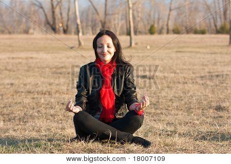 Girl Meditates On A Grass
