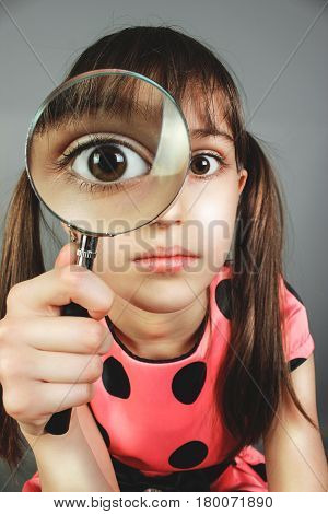little child girl searching with magnifying glass