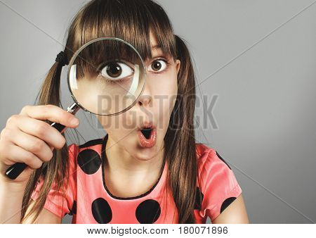surprised little girl searching with magnifying glass