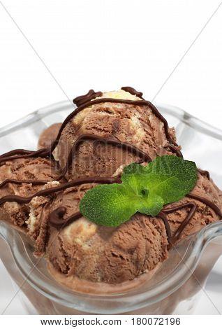 macro of brown ice cream scoops in ramekin on white