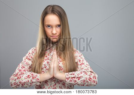 fitness, sport, yoga and healthy lifestyle concept - close up of girl meditating in easy pose. Pretty model looking at camera on gray dackground