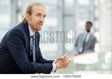 Young confident employer or business leader on background of colleague