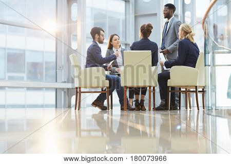 Team of contemporary young co-workers discussing business documents at meeting