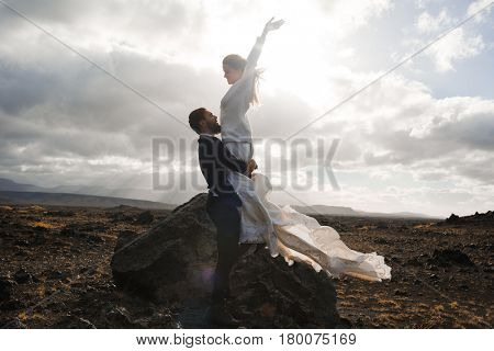 Ecstatic bride held by young man