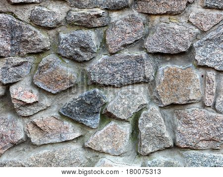 Seamless texture of a stone wall. Granite stone paving stone wall background. Abstract background of old stone cobblestone close-up.