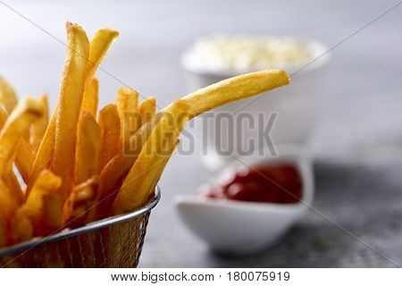 closeup of some appetizing french fries served in a metal basket and some bowls with mayonnaise and ketchup in the background on a gray rustic wooden table