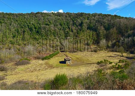 a view of the crater of the Santa Margarida Volcano in the Garrotxa Volcanic Zone Natural Park, in Olot, Spain, with the old small church dedicated to Saint Margaret in the center