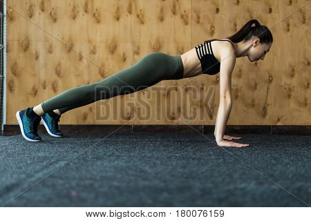Full-length Side View Of Young Beautiful Woman In Sportswear Doing Plank At Gym