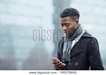 Portrait of handsome African - American businessman using smartphone phone in snowy autumn city street, typing text message and looking at screen